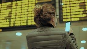 Θηλυκός ταξιδιώτης στο τερματικό αερολιμένων με το τηλέφωνο απόθεμα βίντεο