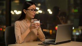 Θηλυκό άρθρο δακτυλογράφησης δημοσιογράφων σχετικά με το lap-top, καφές κατανάλωσης για την έμπνευση απόθεμα βίντεο