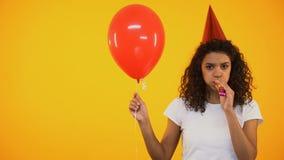Θηλυκό μπαλόνι εκμετάλλευσης και φυσώντας κέρατο κομμάτων, που αισθάνονται μόνα στα γενέθλια απόθεμα βίντεο
