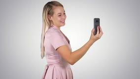 Θηλυκό στο ρόδινο φόρεμα που κάνει την τηλεοπτική κλήση με το έξυπνο τηλέφωνό της στο υπόβαθρο κλίσης φιλμ μικρού μήκους