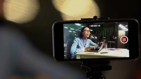 Θηλυκό τηλεοπτικό blogger που καταγράφει το giveaway βίντεο, που παρουσιάζει μετρητά δολαρίων στη κάμερα απόθεμα βίντεο