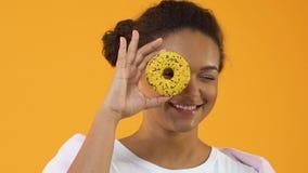 Θηλυκό hipster χαμόγελου που κρατά το κίτρινο doughnut μέτωπο του ματιού, επιδόρπιο ζάχαρης, πρόχειρο φαγητό φιλμ μικρού μήκους