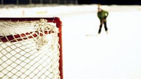 Θολωμένος συνδετήρας της υπαίθριας αίθουσας παγοδρομίας πάγου τη νύχτα με το πατινάζ αγοριών και τον πυροβολισμό της σφαίρας απόθεμα βίντεο