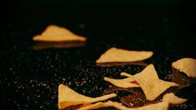 Θρυμματιμένος tortilla πτώση τσιπ κάτω στο μαύρο κλίμα, σε αργή κίνηση πυροβολισμός απόθεμα βίντεο