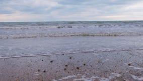 Θυελλώδη κύματα με τον αφρό στη θάλασσα Παραλία άμμου το χειμώνα απόθεμα βίντεο