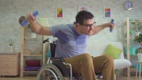 Ισχυρός παραλυμένος αρσενικός αθλητής αναπηρικών καρεκλών στον ιδρώτα που κάνει τους αλτήρες απόθεμα βίντεο