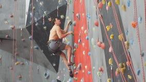 Ισχυρό άτομο που απολαμβάνει την αναρρίχηση βράχου, σε αργή κίνηση φιλμ μικρού μήκους