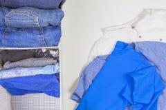 Κάθετη αποθήκευση του ιματισμού, τακτοποίηση, έννοια καθαρισμού δωματίων Σωρός της διπλωμένων μπλούζας και των τζιν στο καλάθι με στοκ φωτογραφίες