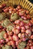 Κάθετη εικόνα των δεσμών των φρέσκων κόκκινων κρεμμυδιών στο καλάθι στοκ φωτογραφίες