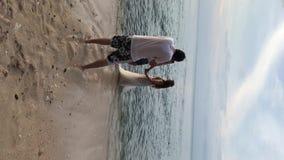 Κάθετο βίντεο Φωτογράφοι που παίρνουν τις φωτογραφίες της νύφης και του νεόνυμφου που περπατούν στην παραλία κοντά στη θάλασσα Γά απόθεμα βίντεο