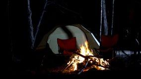 Κάψιμο, σκηνή και καρέκλες πυρών προσκόπων γύρω, διαφήμιση στους γύρους στρατοπέδευσης στο ξύλο στοκ φωτογραφία με δικαίωμα ελεύθερης χρήσης