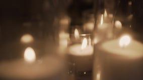 Κάψιμο του διακοσμητικού κεριού στο κηροπήγιο γυαλιού σε ένα θολωμένο υπόβαθρο φιλμ μικρού μήκους