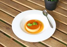 Κέικ κρέμας καραμέλας με peppermint το φύλλο στο άσπρο πιάτο στον ξύλινο πίνακα στοκ εικόνα