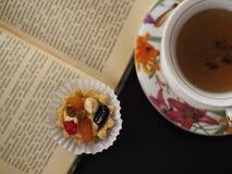 Κέικ με τη βουτύρου κρέμα και φρούτα κοντά σε ένα φλυτζάνι του τσαγιού στο ανοιγμένο βιβλίο στοκ εικόνα με δικαίωμα ελεύθερης χρήσης