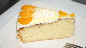 Κέικ σφουγγαριών που διακοσμείται με το ροδάκινο και tangerines στοκ εικόνες με δικαίωμα ελεύθερης χρήσης