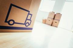 κίνηση Χαρτόνι, κιβώτια για την κίνηση σε ένα νέο, καθαρό και φωτεινό σπίτι στοκ εικόνα