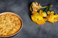 Κίτρινες λουλούδι, μπισκότα και πίτα μήλων που βρίσκεται στο γκρίζο υπόβαθρο στοκ εικόνα