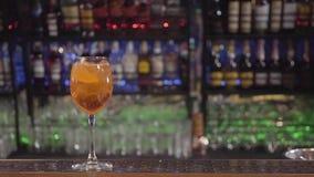 Κίτρινο κοκτέιλ στο γυαλί κρασιού με το πορτοκάλι στο φραγμό Μπουκάλια του οινοπνεύματος στο υπόβαθρο απόθεμα βίντεο