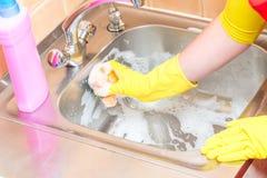 Καθαρισμός του ανοξείδωτου νεροχύτη κουζινών με τον αφρό στοκ εικόνα με δικαίωμα ελεύθερης χρήσης