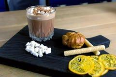 Κακάο με marshmallow στο γυαλί βράχου σε έναν ξύλινο μαύρο δίσκο με το κέικ και το λεμόνι πλάγια όψη κινηματογραφήσεων σε πρώτο π στοκ φωτογραφίες με δικαίωμα ελεύθερης χρήσης