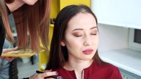 Καλλιτέχνης Makeup που εφαρμόζει τη σκιά ματιών στα μάτια μιας νέας γυναίκας φιλμ μικρού μήκους
