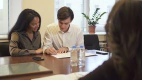 Καλό multiethnic ζεύγος στο γραφείο αντιπροσωπειών ακίνητων περιουσιών που υπογράφει τη σύμβαση υποθηκών φιλμ μικρού μήκους