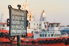 Καμία πινακίδα ρύπανσης που γράφεται στα ελληνικά παρακαλώ, δεν ρίχνει τα απορρίματα στη θάλασσα που τοποθετείται στην προκυμαία  στοκ εικόνα