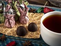 Καραμέλες σοκολάτας, μαύρο τσάι στοκ φωτογραφίες