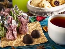Καραμέλες σοκολάτας, μαύρο τσάι στοκ εικόνα με δικαίωμα ελεύθερης χρήσης
