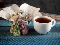 Καραμέλες σοκολάτας, μαύρο τσάι στοκ εικόνες