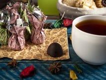 Καραμέλες σοκολάτας, μαύρο τσάι στοκ εικόνα