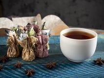 Καραμέλες σοκολάτας, μαύρο τσάι στοκ φωτογραφία