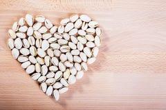 Καρύδια φυστικιών που διαμορφώνουν μια καρδιά-μορφή στο ξύλινο υπόβαθρο πατωμάτων στοκ φωτογραφία με δικαίωμα ελεύθερης χρήσης