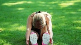 Κατάλληλη γυναίκα που κάνει την τεντώνοντας γυμναστική στην πράσινη χλόη στο θερινό πάρκο απόθεμα βίντεο
