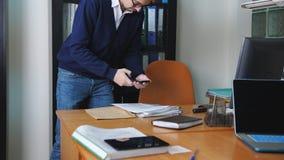 Κατάσκοπος στο τηλέφωνο που παίρνει τις εικόνες των μυστικών αρχείων στο γραφείο απόθεμα βίντεο