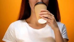 Καφές κατανάλωσης κοριτσιών, δαπάνη πρωινού με την ενέργεια και καλό πορτοκαλί υπόβαθρο διάθεσης στοκ φωτογραφία