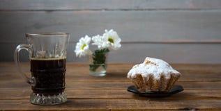 Καφές cupcake και λουλούδια σε ένα ξύλινο υπόβαθρο στοκ φωτογραφία