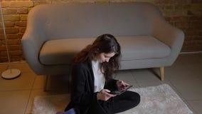 Καυκάσιο κορίτσι με την κυματιστή συνεδρίαση τρίχας brunette στην προσοχή πατωμάτων προσεκτικά στην ταμπλέτα στην άνετη εγχώρια α φιλμ μικρού μήκους
