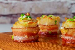 Καυτές ψημένες πατάτες με το τυρί, το μπέϊκον και το κρεμμύδι sclose-επάνω στο ξύλινο υπόβαθρο στοκ εικόνα