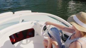 Καπέλο γυναικών turit που επιπλέει σε μια βάρκα, που χρησιμοποιεί ένα κινητό τηλέφωνο επάνω από την όψη Έννοια: διακοπές θάλασσας απόθεμα βίντεο