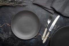 Κενό γκρίζο πιάτο κεραμικό σε ένα σκούρο γκρι υπόβαθρο με ένα μαχαίρι και ένα δίκρανο, που διακοσμούνται με μια ανθοδέσμη lavende στοκ φωτογραφίες