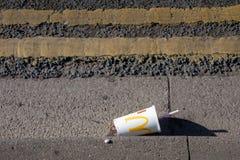 Κενό φλυτζάνι εγγράφου McDonalds στην πλευρά του δρόμου με τις διπλές κίτρινες γραμμές στοκ εικόνα