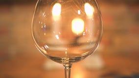 Κενό wineglass στο κάψιμο του υποβάθρου κεριών Κλείστε επάνω το γυαλί κρασιού στον πίνακα γευμάτων βραδιού με τα κεριά φιλμ μικρού μήκους