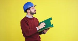 _κεφάλι περιοχή νεαρός άνδρας ο στούντιο με ένας κίτρινος υπόβαθρο τοίχος με ένας ασφάλεια μπλε κράνος ανα:λύω κάτι και φιλμ μικρού μήκους