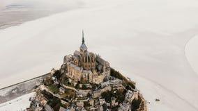 Κηφήνας που μεγεθύνει έξω, πετώντας επάνω και μακρυά από στο επικό ορόσημο αβαείων νησιών Mont Saint-Michel κατά τη διάρκεια της  απόθεμα βίντεο