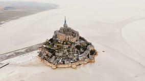 Κηφήνας που πετά αριστερά γύρω από τη μεγαλοπρεπή πόλη νησιών Mont Saint-Michel, διάσημο ορόσημο κατά τη διάρκεια της χαμηλής παλ απόθεμα βίντεο