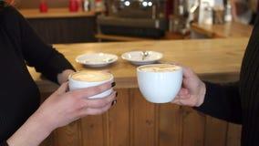 Κινηματογράφηση σε πρώτο πλάνο ενός άνδρα και μιας γυναίκας που κρατούν ένα φλυτζάνι του ευώδους cappuccino Τέχνη Latte απόθεμα βίντεο