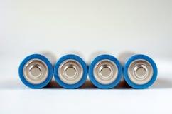 Κινηματογράφηση σε πρώτο πλάνο τεσσάρων μπλε-χρυσή μπαταριών AA σε ένα άσπρο υπόβαθρο Ρηχό βάθος του τομέα, μακροεντολή στοκ εικόνα