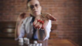 Κινηματογράφηση σε πρώτο πλάνο του χαπιού καψών στο χέρι του γιατρού γυναικών απόθεμα βίντεο