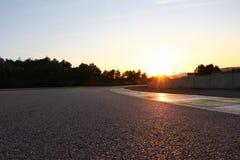 Κινηματογράφηση σε πρώτο πλάνο του tarmac στη πίστα αγώνων κατά τη διάρκεια του ηλιοβασιλέματος στοκ εικόνες